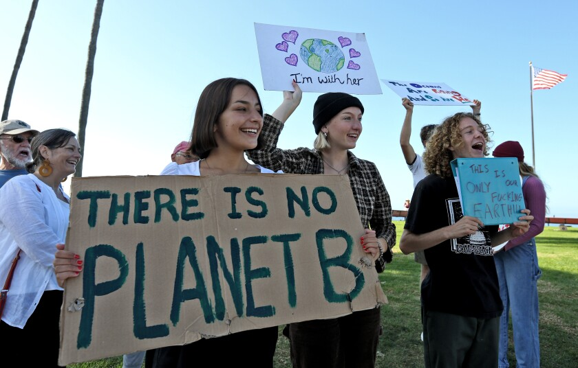 """Demonstrators hold a sign saying """"There is No Planet B""""  during a 2019 protest at Huntington Beach High School"""