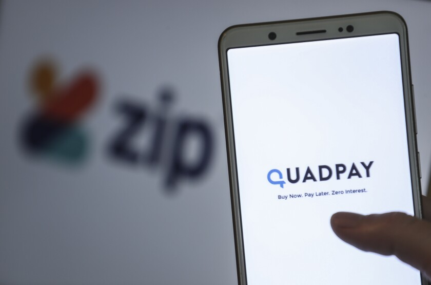 The words Quadpay: Buy Now. Pay Later. Zero Interest. appear on a smartphone screen