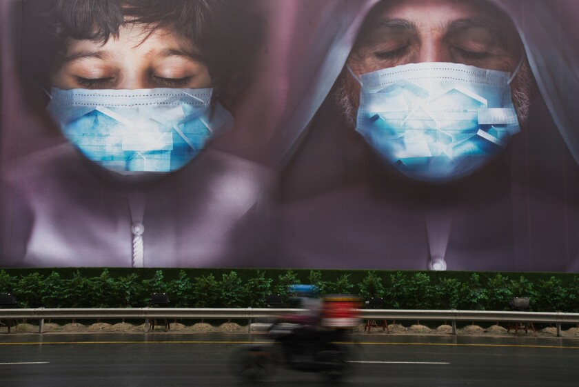 Masked faces on a billboard.