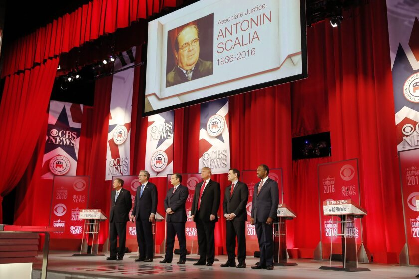 John Kasich, Jeb Bush, Ted Cruz, Donald Trump, Marco Rubio and Ben Carson take the stage beneath an image of U.S. Supreme Court Justice Antonin Scalia, who died earlier in the day.