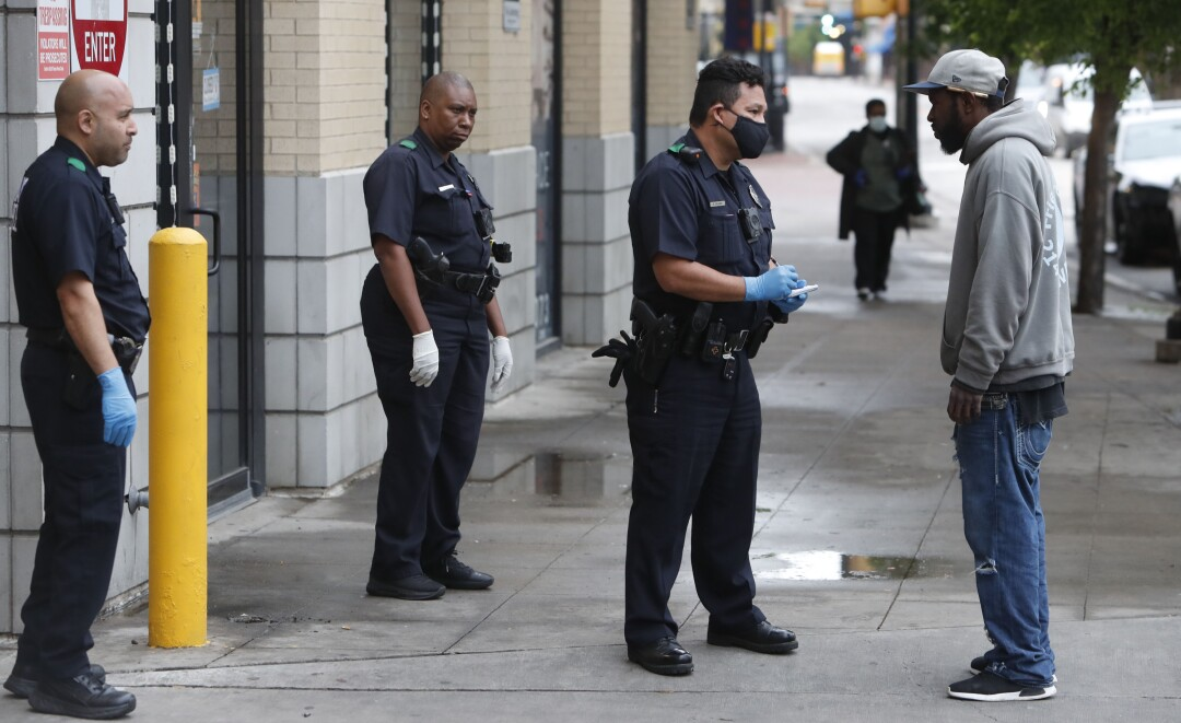 TEXAS: Practicing social distancing amid coronavirus concerns, police officers speak with a man in downtown Dallas.