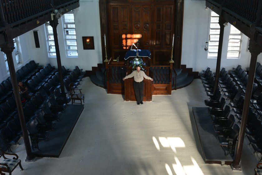 In this Feb. 27, 2015 photo, Jamaican Jewish community leader Ainsley Henriques poses for a photo on the sand covered floor of Sha'are Shalom, Jamaica's last synagogue, in Kingston. The dwindling congregation of the historic Kingston temple is trying to preserve their history and attract tourists w