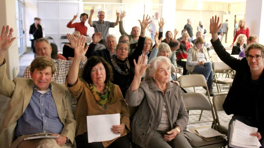Airport Noise Advisory Committee meeting attendees raise their hands to answer the question, 'Who in this room is from La Jolla?' The meeting took place Feb. 15 at the San Diego International Airport Administration Building.
