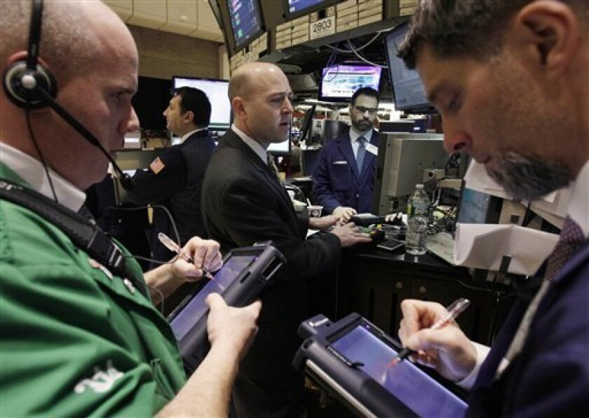 In this Feb. 1, 2012 photo, specialist Jay Woods, center, works at his post on the floor of the New York Stock Exchange. Markets took a breather on Thursday, Feb. 2, 2012, following solid gains in the previous session, as investors positioned themselves for crucial U.S. jobs data that often set the tone for a week or two after their release. (AP Photo/Richard Drew)
