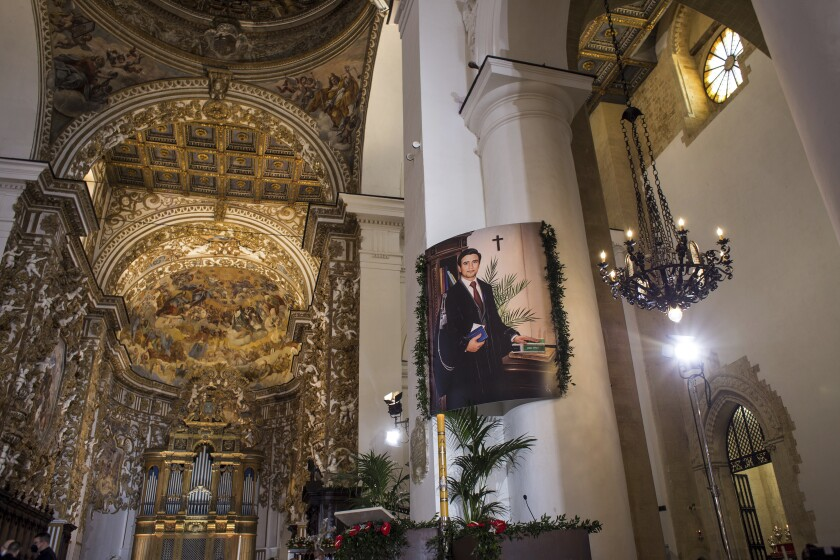 """A picture of late magistrate Rosario Livatino is displayed during a beatification ceremony at the cathedral of Agrigento, southern Italy, Sunday, May 9, 2021. A magistrate slain by mobsters in Sicily and praised by two popes has been beatified by the Roman Catholic church on Sunday in the last formal step before possible sainthood. Rosario Livatino was gunned down on a Sicilian highway outside Agrigento as he drove to work in 1990. Three years later, during a pilgrimage to Sicily, Pope John Paul II hailed him a """"martyr of justice and, indirectly, of the Christian faith."""" (Fabio Peonia/LaPresse via AP)"""