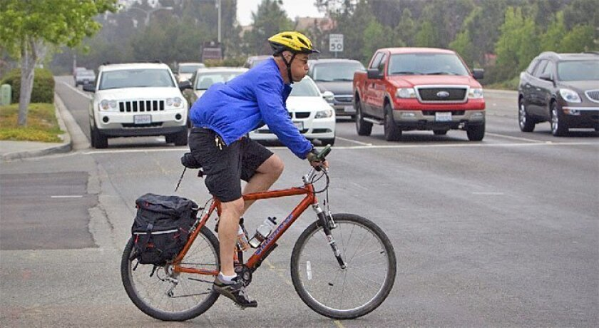 John Orcutt made his way through traffic on Bike to Work Day yesterday on his way to Rancho del Rey Middle  School in Chula Vista, where he teaches. (Nelvin C. Cepeda / Union-Tribune)