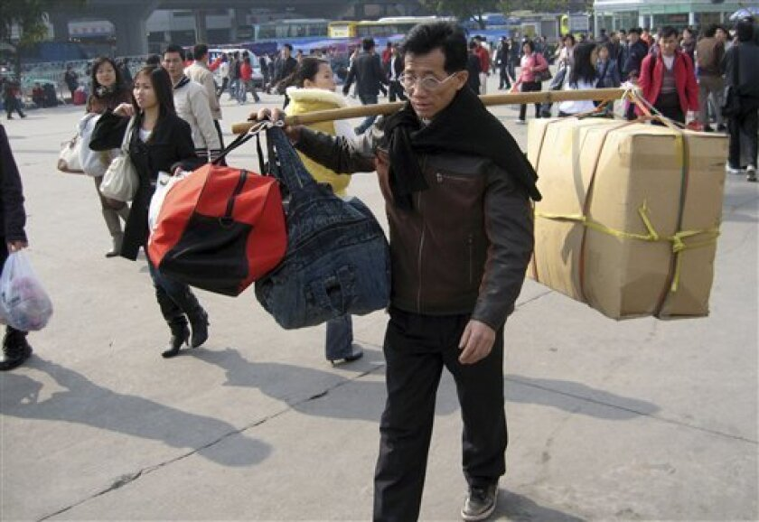 A migrant worker nears the train station in Guangzhou, southern China's Guangdong province, Thursday, Jan. 8, 2009. Some 188 million Chinese are expected to squeeze onto China's train network in the coming weeks to return home for the Chinese Lunar New Year.  (AP Photo/William Foreman)