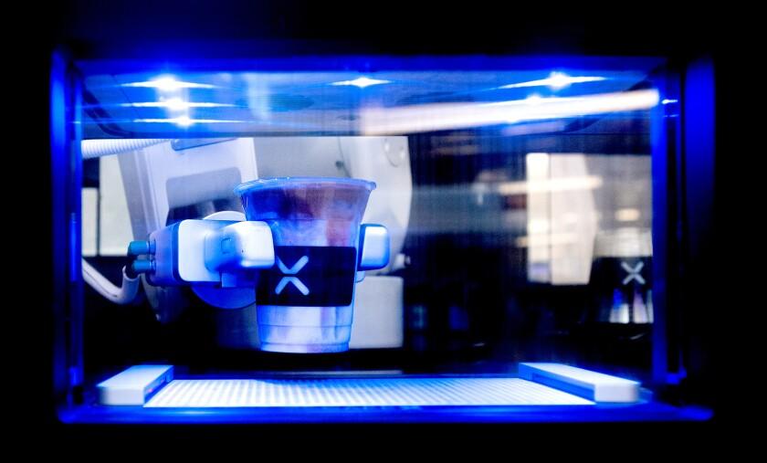 A Cafe X robot dispenses a cappuccino at San Francisco International Airport.