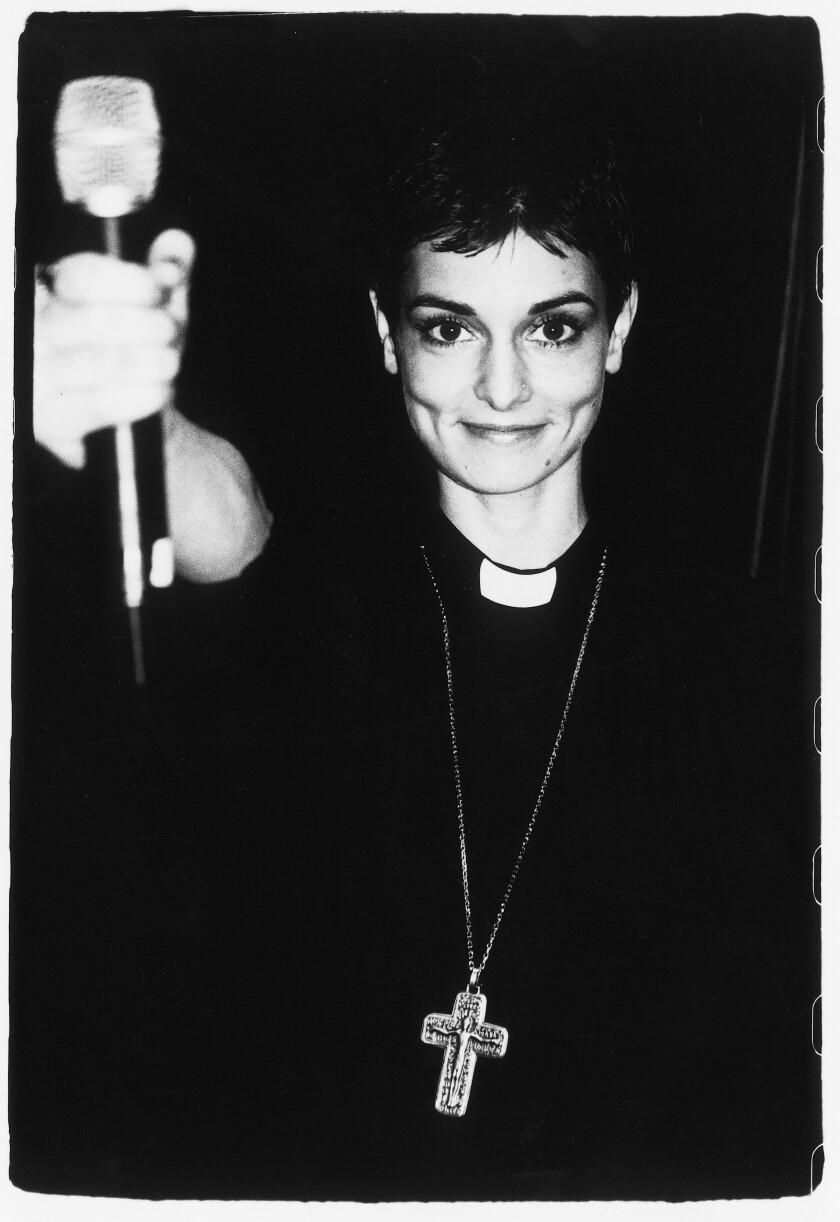 A vintage photo of Sinéad O'Connor wearing a priest's collar and crucifix.