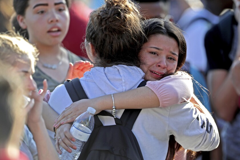 Students released from a lockdown embrace following a shooting at Marjory Stoneman Douglas High School in Parkland, Fla.