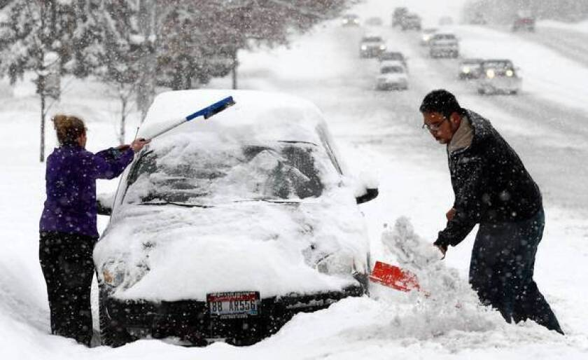 Residents of Ogden, Utah, clear snow after close to a foot fell in the area Friday. A federal report on climate change described devastating weather linked to global warming.