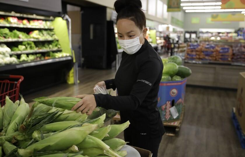 La trabajadora de la aplicación Instacart, Saori Okawa, compra verduras para entregarlas en casa el miércoles 1 de julio de 2020 en San Leandro, California. (AP Foto/Ben Margot)