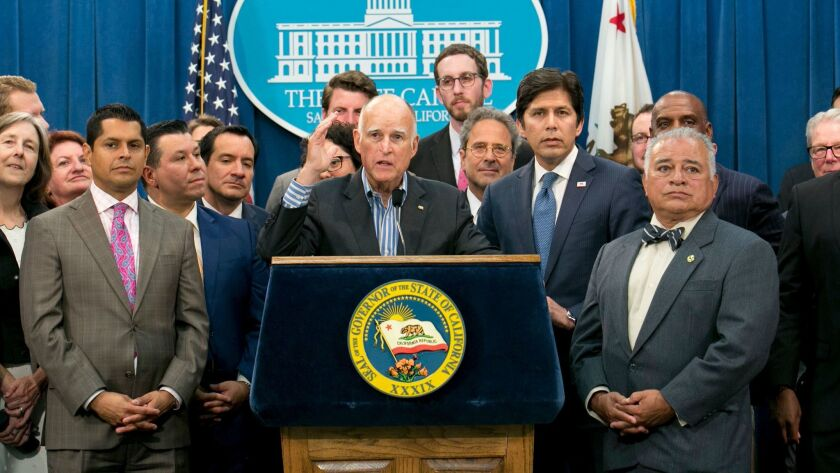 Gov. Jerry Brown, center, flanked by lawmakers from both sides of the aisle, speaks of the passage o