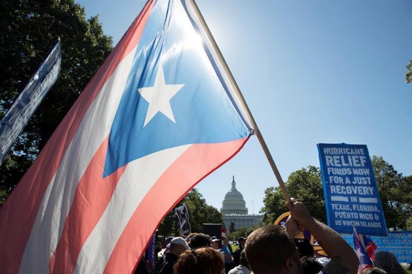Un hombre sostiene la bandera de Puerto Rico durante el discurso de la senadora democrática por Massachusetts Elizabeth Warren, en una manifestación que demanda el rescate de aquellos afectados por el huracán Irma, María y Harvey, en las inmediaciones del Capitolio de Washington (Estados Unidos), el 18 de octubre de 2017. EFE/Archivo