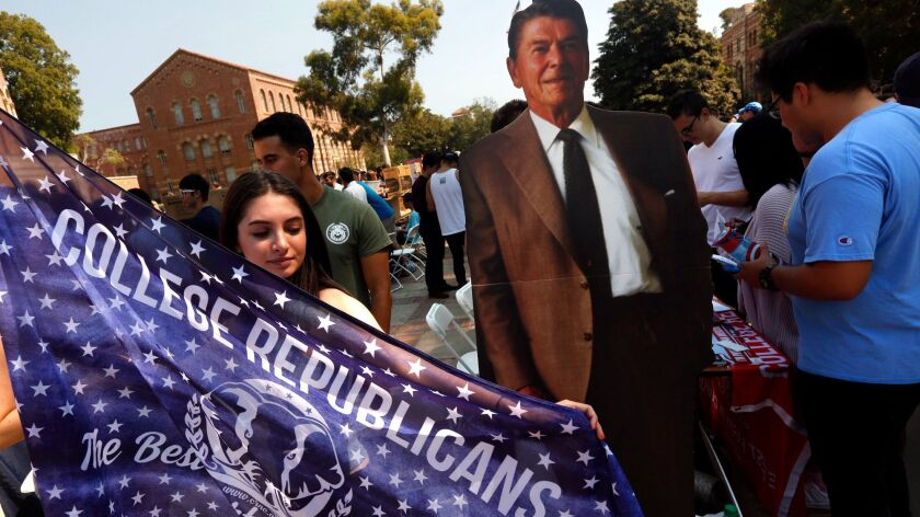 UCLA senior Emma Bock, 20, stands next to a cardboard figure of President Reagan as she and other Bruin Republicans recruit members at UCLA's annual student involvement fair.