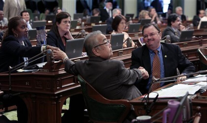 Assemblyman Warren Furutani, D-Lakewood, center,  receives congratulations from Assemblywoman Holly Mitchell, D- Hollywood, left, and Assemblyman Rich Gordon, D-Menlo Park after his pension reform bill was approved by the Assembly at the Capitol in Sacramento, Calif.,  Friday, Aug. 31, 2012.  The m