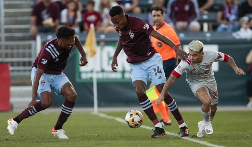 Colorado Rapids defender Auston Trusty, left, and midfielder Mark-Anthony Kaye (14) keep Toronto FC midfielder Yeferson Soteldo (30) away from the ball in the first half of an MLS soccer game in Denver, Saturday, Sept. 25, 2021. (AP Photo/Joe Mahoney)