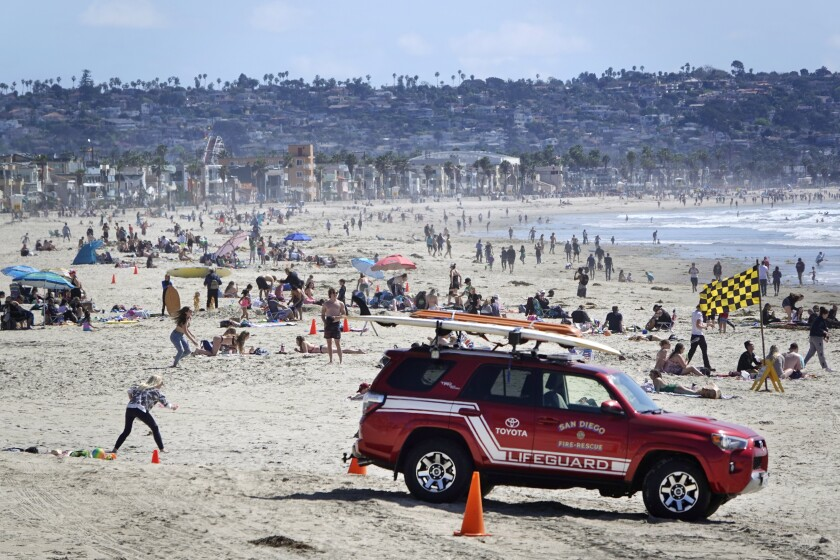 Beach goers enjoy a sunny day in Pacific Beach on March 17, 2020.