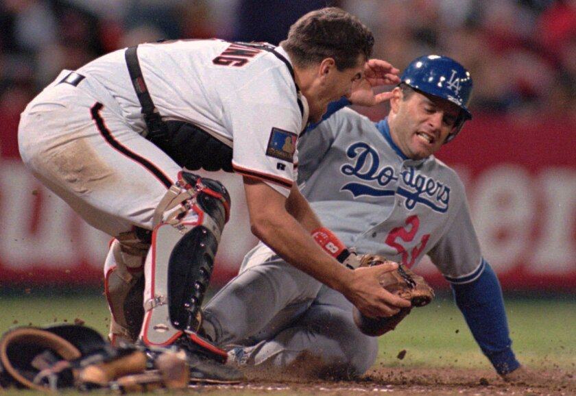 Dodgers first baseman Eric Karros slides beneath the tag of San Francisco Giants catcher Kirt Manwaring to score during a game on July 25, 1994, at Candlestick Park.