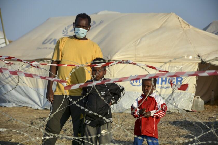 Un adulto y dos niños migrantes observan desde el interior del nuevo campamento temporal