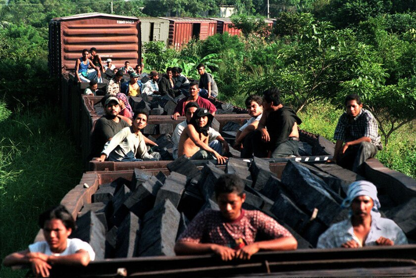 Undocumented Central Americans crowd the tops of freight train cars in Mexico.