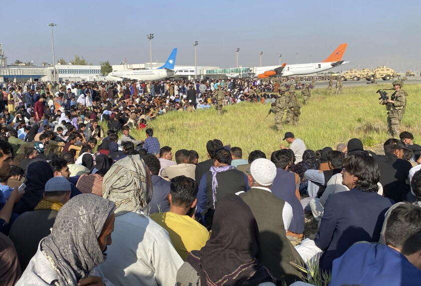 People sit on the ground near airplanes as troops stand and watch.