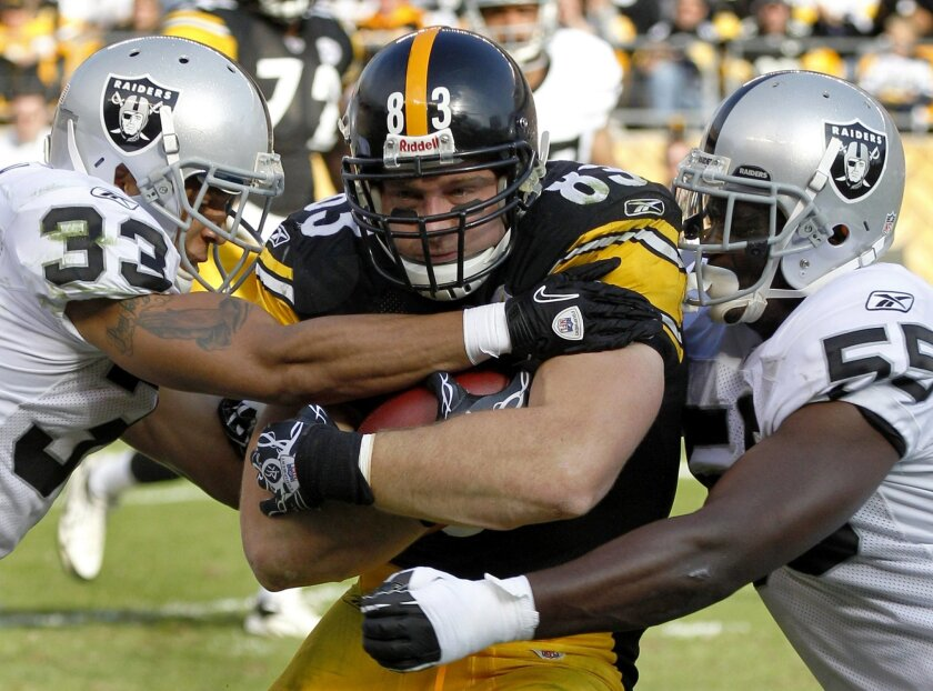 FILE - In this file photo from Nov. 21, 2010, Pittsburgh Steelers tight end Heath Miller (83) is stopped by Oakland Raiders' Tyvon Branch (33) and Rolando McClain (55) after a short gain during the first quarter of an NFL football game in Pittsburgh. Steelers tight end Heath Miller retired on Frida