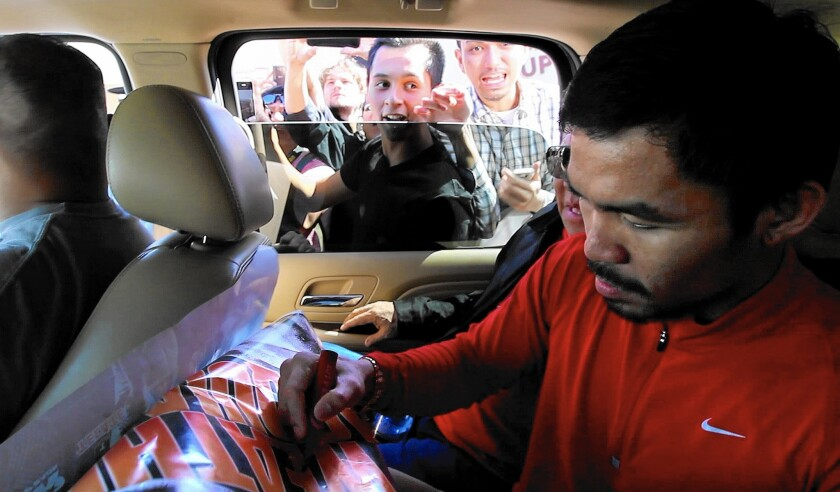 Manny Pacquiao signs a poster for a fan as he leaves Wild Card Boxing Gym in Hollywood on April 27, before heading to Las Vegas.