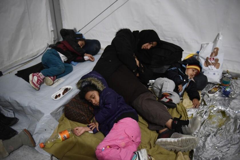 Una madre duerme con sus hijos dentro de una tienda de campaña en un campamento para refugiados. Miles de inmigrantes que huyen de la guerra buscan llegar a países europeos prósperos como Alemania, Austria y Suecia. (Foto AP/Giannis Papanikos)