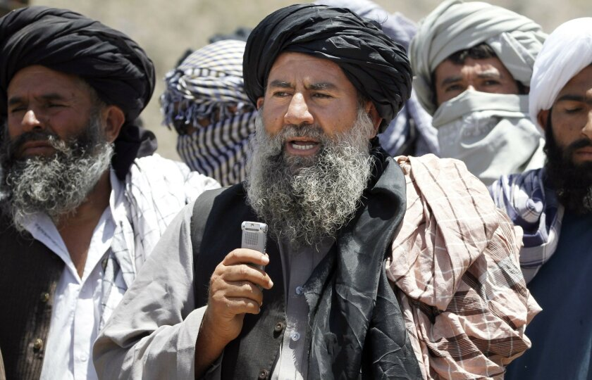 In this Friday, May 27, 2016 photo, Senior leader of a breakaway faction of the Taliban Mullah Abdul Manan Niazi, center, delivers a speech to his fighters, in Shindand district of Herat province, Afghanistan. Niazi said Sunday, May 29, 2016 it was willing to hold peace talks with the Afghan govern