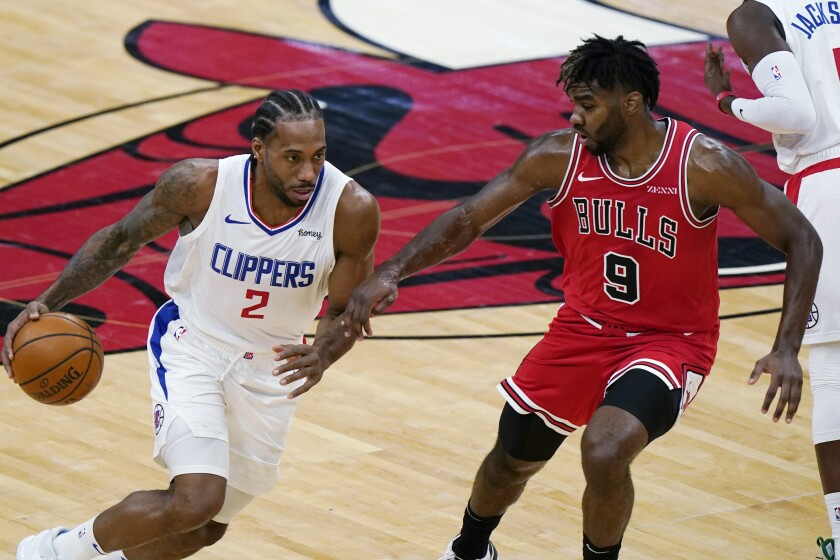 Los Angeles Clippers forward Kawhi Leonard, left, drives against Chicago Bulls forward Patrick Williams during the second half of an NBA basketball game in Chicago, Friday, Feb. 12, 2021. (AP Photo/Nam Y. Huh)