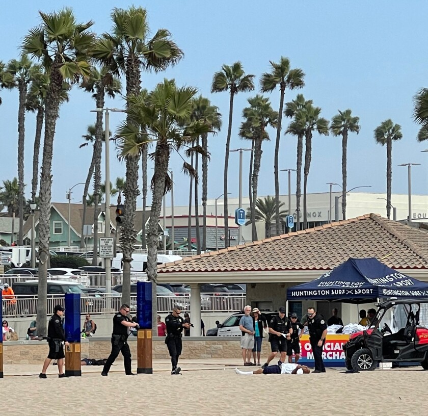 Police surround Ronnie Andrew Garcia on Saturday afternoon at Huntington City Beach.