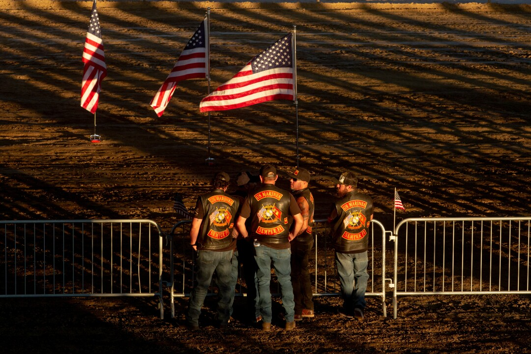 Some men in leather vests stand outside near U.S. flags as the sun sets