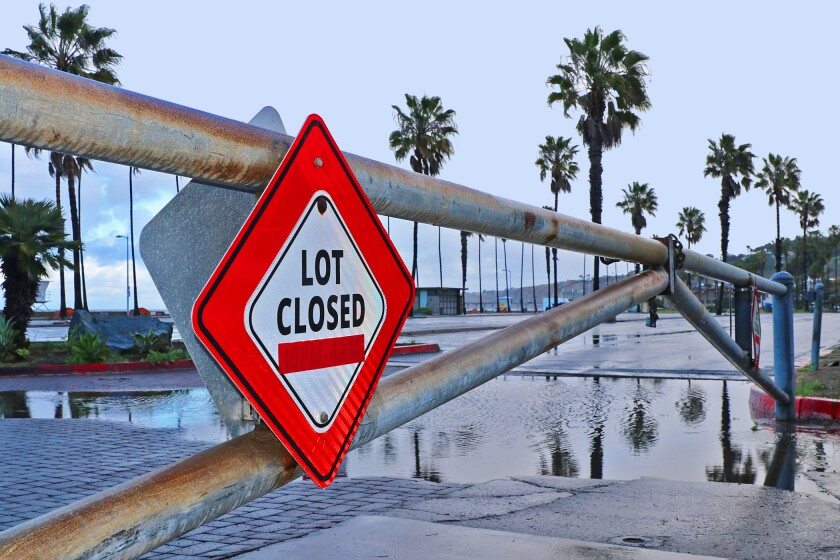 "A gate to the parking lot at La Jolla Shores Beach with a ""LOT CLOSED"" sign."