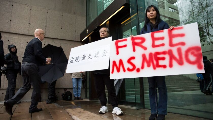 Ada Yu, right, and Robert Long hold signs in support of Huawei Technologies Chief Financial Officer Meng Wanzhou outside the courthouse in Vancouver, Canada, during her bail hearing Tuesday.