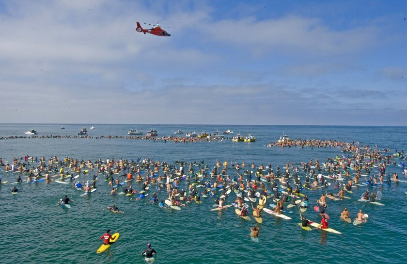 A Coast Guard helicopter hovers over people gathered for a memorial for Newport Beach lifeguard, Ben Carlson off the Newport Pier Sunday, July 13, 2014 in Newport Beach, Calif. Carlson drowned July 6, while trying to rescue a swimmer off Newport Beach. He was trying to help a struggling swimmer when they were hit by a large wave. The swimmer made it to shore safely, but the 32-year-old lifeguard went under. Carlson was a 15-year veteran of the Newport Beach Fire Department. (AP Photo/Orange County Register, Michael Goulding)