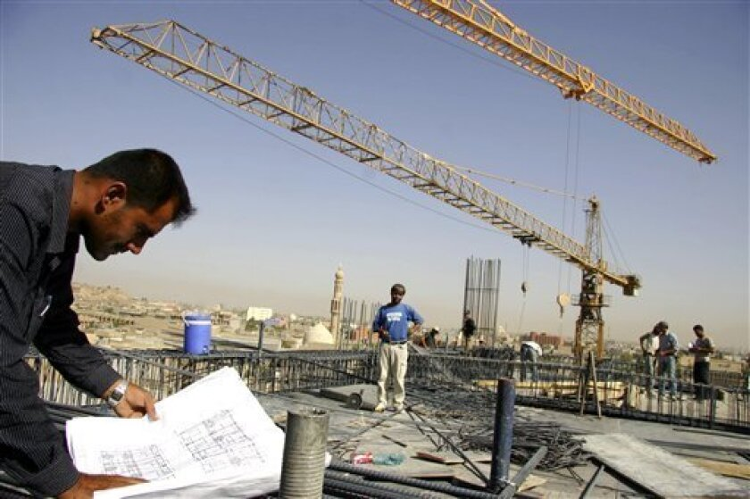 FILE - In this Sept. 19, 2007, file photo, a worker looks at blueprints at a construction site in Irbil, Iraq. In the decade since U.S.-led forces toppled Iraqi dictator Saddam Hussein, Kurds have trained their sights toward Turkey and the West, at the expense of ties with the still largely dysfunctional rest of the country. (AP Photo/Yahya Ahmed, File)