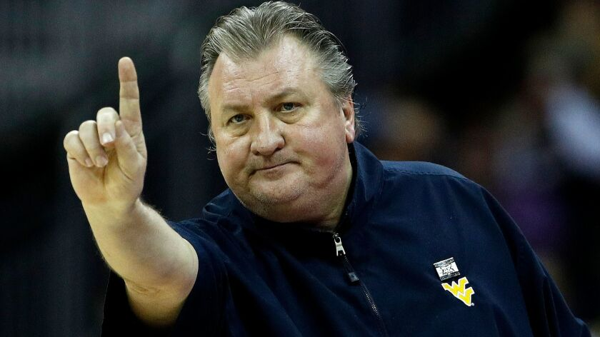 West Virginia head coach Bob Huggins motions to his players during the first half of the NCAA colleg