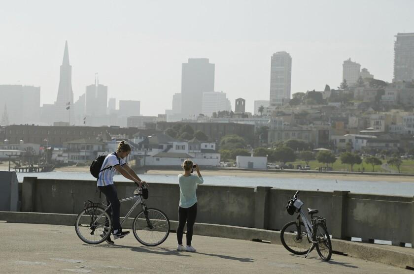 ARCHIVO - En esta foto de archivo del 17 de agosto de 2015, una pareja toma fotos de San Francisco desde el Parque Acuático. Un hombre de 20 años fue muerto a tiros cuando jugaba Pokémon Go en el lugar el 6 de agosto de 2016. (AP Foto/Eric Risberg, File)