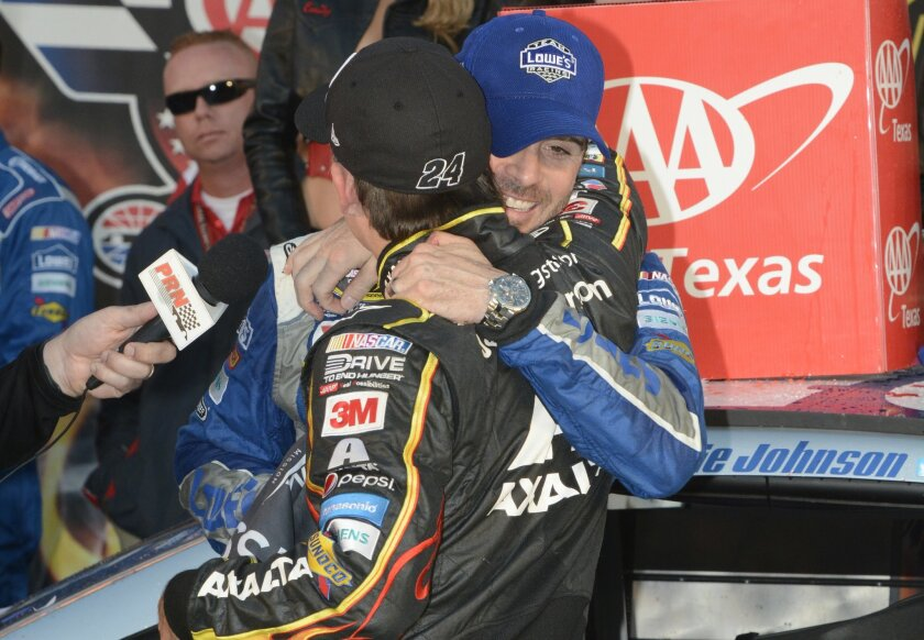 Jimmie Johnson, right, hugs Jeff Gordon in victory lane after Johnson won the NASCAR Sprint Cup Series auto race at Texas Motor Speedway in Fort Worth, Texas, Sunday, Nov. 8, 2015. (AP Photo/Larry Papke)