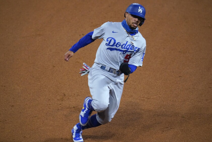 Los Angeles Dodgers' Mookie Betts advances to third on a double by Corey Seager off Colorado Rockies relief pitcher Carlos Estevez during the seventh inning of a baseball game Thursday, Sept. 17, 2020, in Denver. (AP Photo/David Zalubowski)
