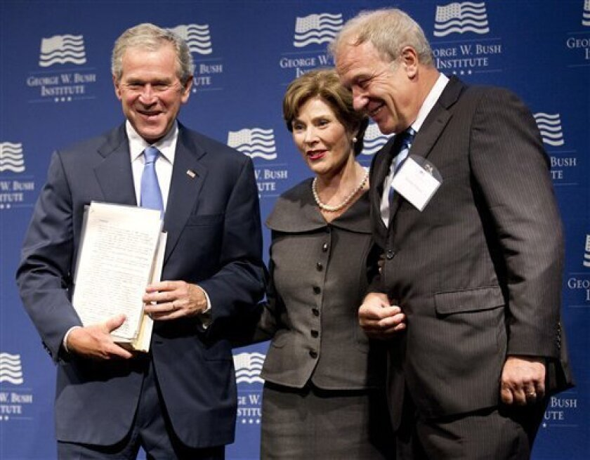 Former President George W. Bush, with former first lady Laura Bush, center, is presented with a collection of writings by former Czech President Vaclav Havel by Martin Palous, head of the Vaclav Havel Library Foundation during a gathering to celebrate the successes of dissidents and activists in th