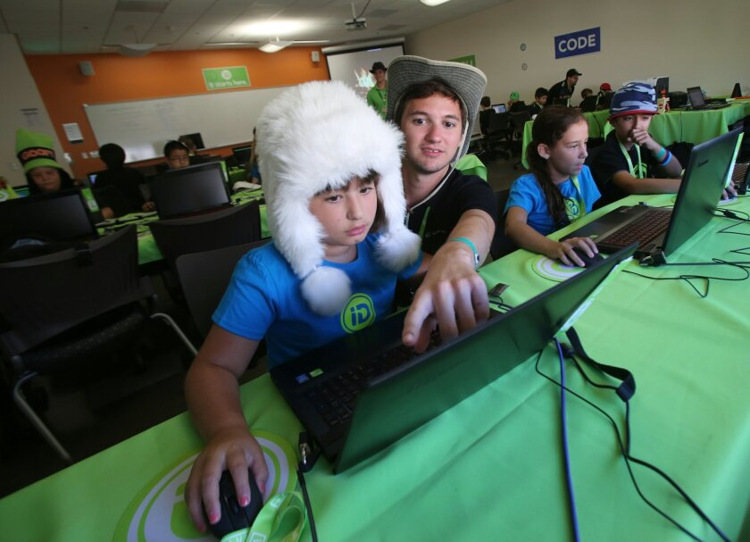 During funny hat day, instructor Taylor Maraz helps a student named Darya work on a computer during science camp held at Cal State University at San Marcos.