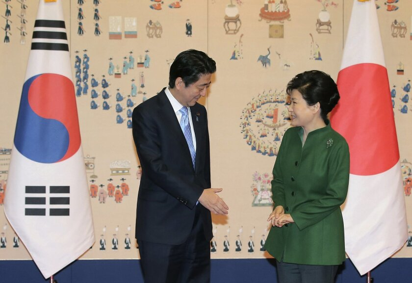 Japanese Prime Minister Shinzo Abe, left, offers his hand to shake hands with South Korean President Park Geun-hye before their meeting at the presidential Blue House in Seoul, South Korea, Monday, Nov. 2, 2015. (Lee Jung-hun/Yonhap via AP) KOREA OUT