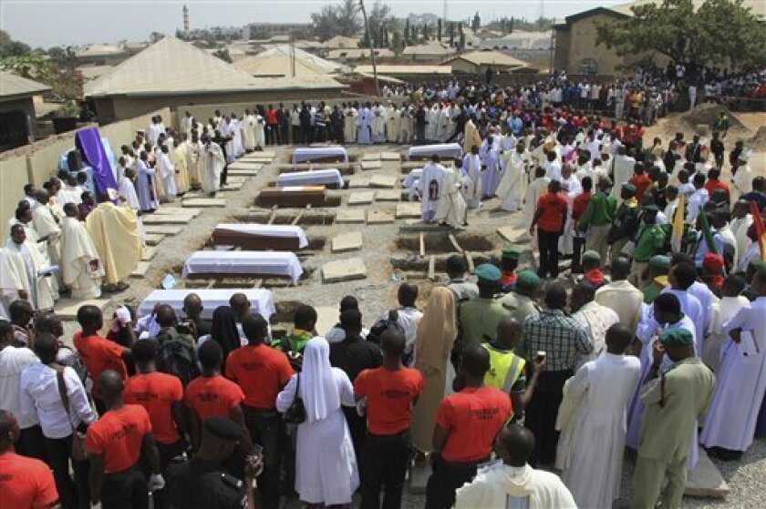 Mourners and priests gather in the back lot of a Catholic church now turned into a mass grave in Madalla, Nigeria, on Wednesday, Feb. 1, 2012. Mourners wept as they carried out the mass burial Wednesday at the church near Nigeria's capital where dozens died in a Christmas Day bombing by a radical Islamist sect.(AP Photo/Sunday Aghaeze)
