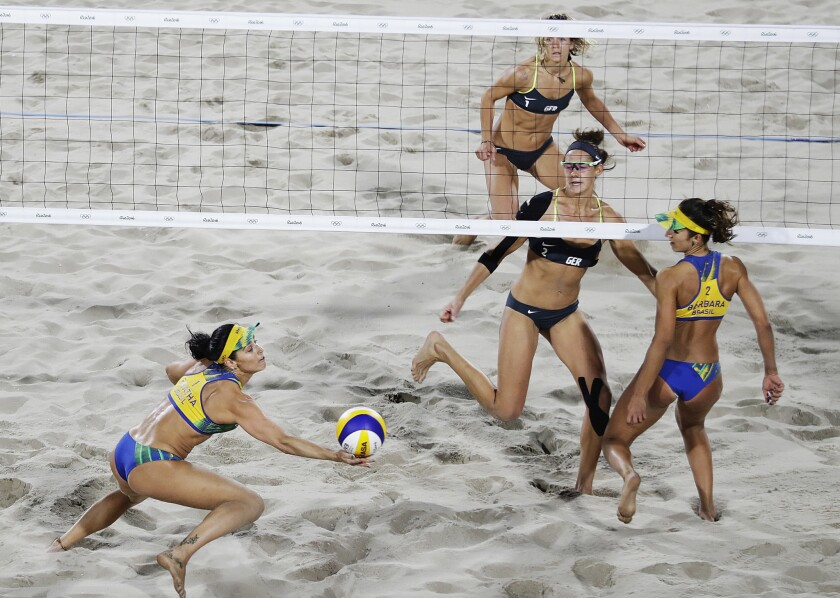 Brazil's Agatha Bednarczuk, left, reaches for a ball hit by Germany's Kira Walkenhorst, center right, as their teammates Barbara Seixas de Freitas, right, and Laura Ludwig, rear, look on during the women's beach volleyball gold medal match at the 2016 Summer Olympics in Rio de Janeiro, Brazil, Thursday, Aug. 18, 2016. (AP Photo/David Goldman)