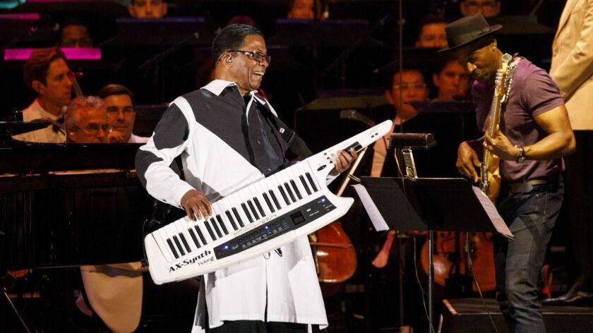 Oscar and Grammy Award-winning music legend Herbie Hancock is as accomplished performing on a guitar-like keytar (above) as he is on a grand piano, an electric piano or an array of state-of-the-art synthesizers. He is shown above at a 2018 Los Angeles concert with bassist Marcus Miller and the Gustavo Dudamel-led Los Angeles Philharmonic, whose jazz programming Hancock oversees.