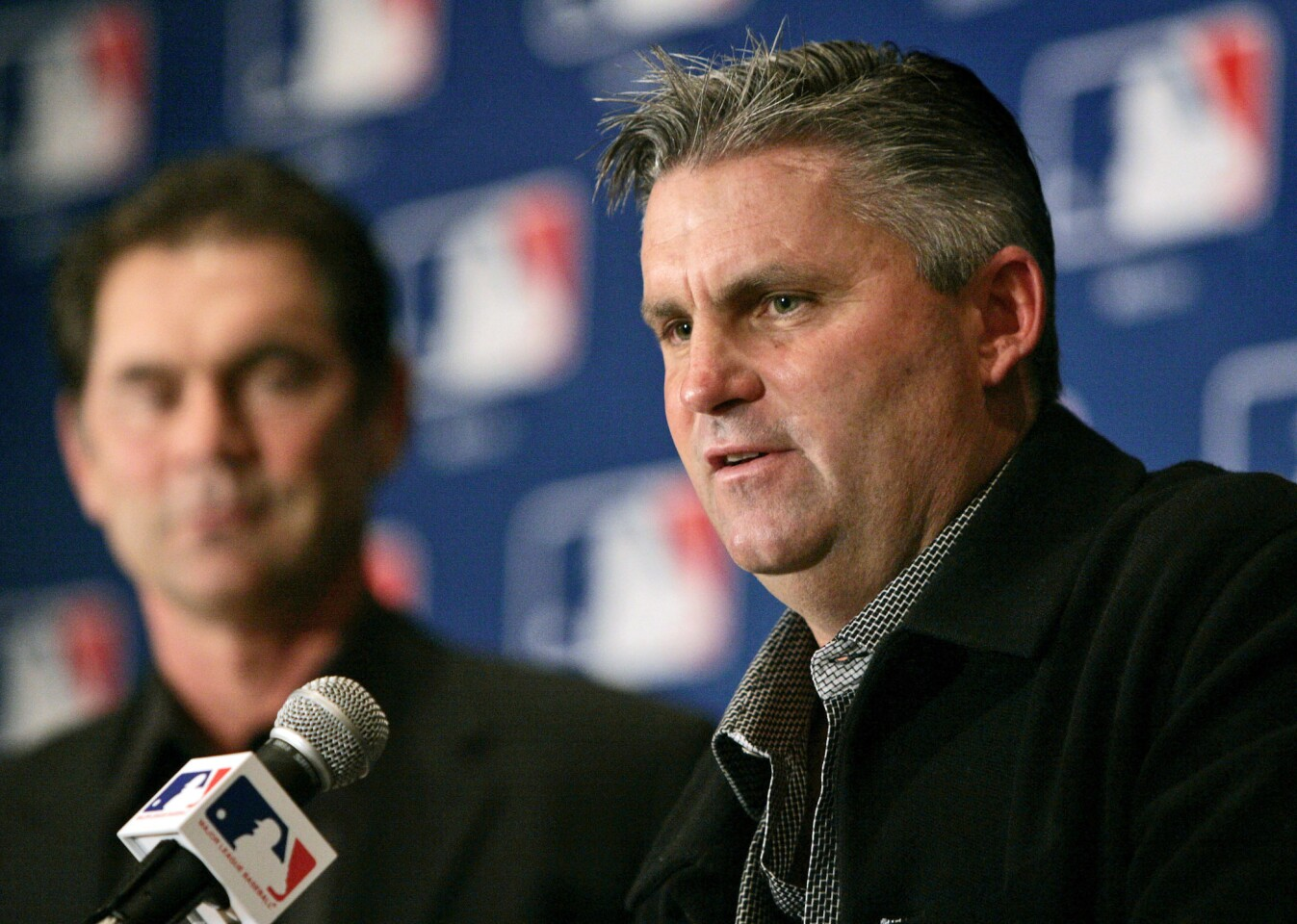 FILE - In this Dec. 7, 2005, file photo, San Diego Padres general manager Kevin Towers, right, peaks during a baseball news conference in Dallas. Towers, whose 14-year tenure as general manager of the San Diego Padres included an appearance in the 1998 World Series, died Tuesday, Jan. 30, 2018, from complications of cancer, friend and former agent Barry Axelrod said. He was 56. (AP Photo/Tony Gutierrez, File)