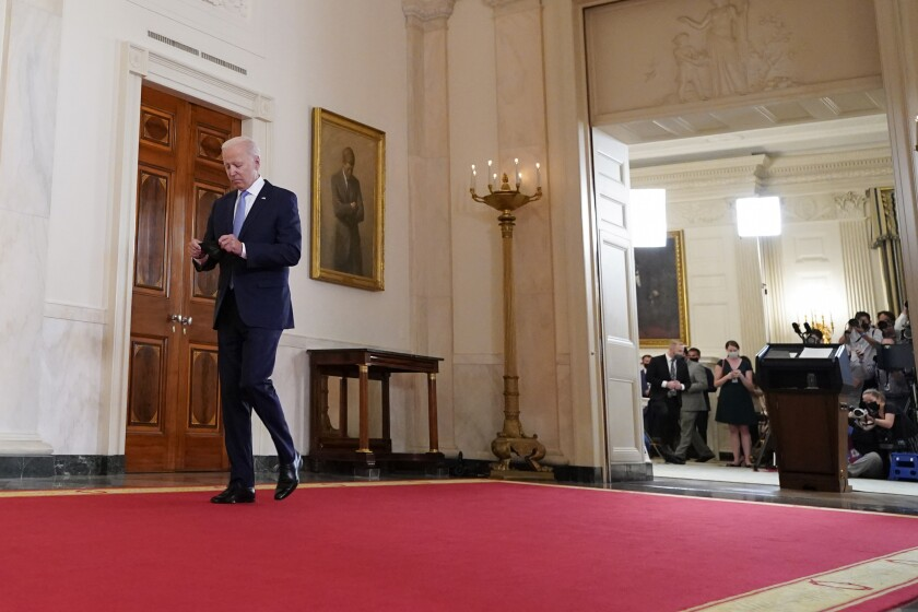 President Biden walks on a red carpet away from a lectern with reporters in front of it