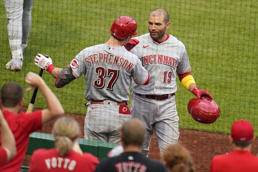 Cincinnati Reds' Joey Votto (19) celebrates with Tyler Stephenson as he returns to the dugout after hitting a three-run home run off Pittsburgh Pirates starting pitcher Cody Ponce (44) during the fifth inning of a baseball game in Pittsburgh, Sunday, Oct. 3, 2021. (AP Photo/Gene J. Puskar)
